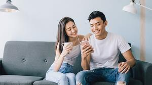 A young couple looks at a mobile phone while sitting on their sofa