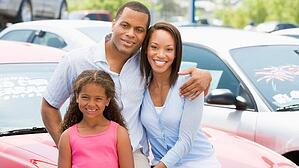 A family stands in front of a vehicle in a car lot