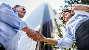Two employees shake hands outside a large building