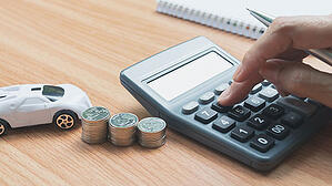 A hand is punching the numbers on a calculator with stacks on coins sitting nearby