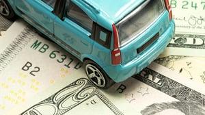 A toy car sits on top of twenty dollar bills