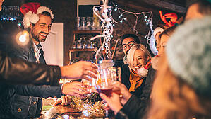 Festive party-goers all raise their glasses