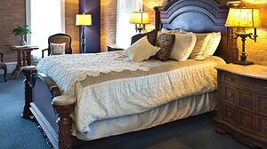 A hotel room with an ornate bed