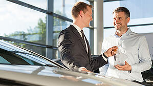 A car salesman hands keys to the new car's owner