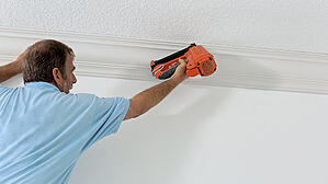 A man uses a nail gun to secure crown molding in a home