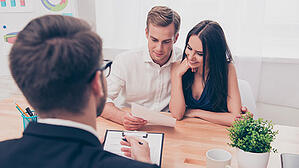 A couple sits at a table meeting with an insurance advisor