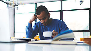 A young man sits reading a book while drinking coffee