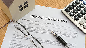 A rental agreement sits on a desk ready to be signed