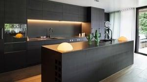 A modern kitchen with dark cabinets
