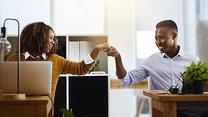 Two employees fist bump in an office