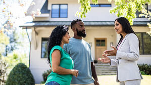 Couple talks with real estate agent in front of home