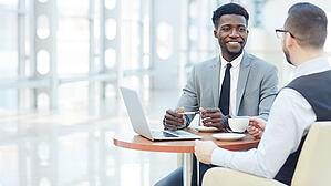 Two businessmen share coffee